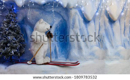 A huge toy polar bear is on skis, and there is snow all around. Christmas card with a picture of a Christmas tree and a bear on skis. Bear skiing christmas, winter banner.