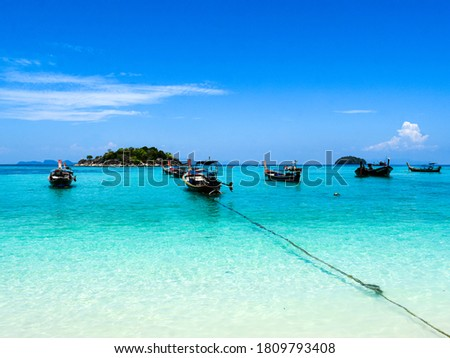 Long tail boats in small harbor at Ko Lipe island south Thailand. Tropic and exotic island is symbol of tropical paradise part of Tarutao national nature park the letters are the name of the boat.