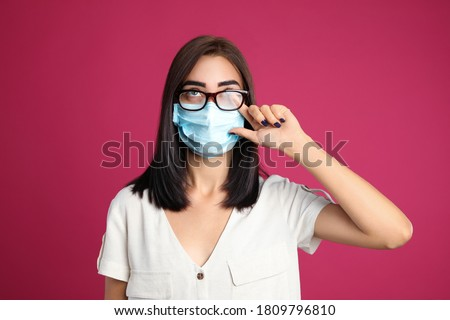 Young woman wiping foggy glasses caused by wearing disposable mask on pink background. Protective measure during coronavirus pandemic Royalty-Free Stock Photo #1809796810