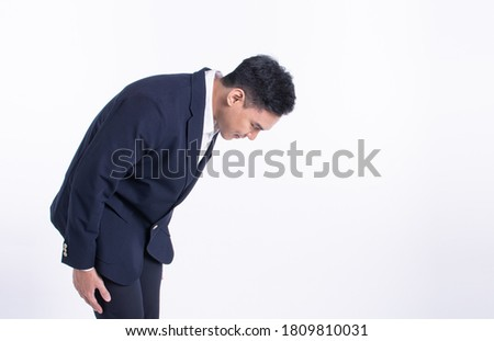 Young asian man wearing formal suit and bowing to pay respect or be sorry while standing on white background with copy space. Business Manner Concept. Royalty-Free Stock Photo #1809810031