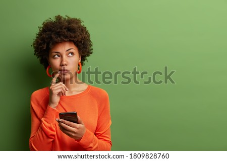 Photo of pretty ethnic woman ponders on how to answer question, thinks deeply about something, uses modern mobile phone, tries to made up good message, keeps index finger near lips, stands indoor #1809828760
