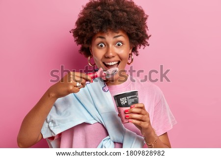 Close up shot of cheerful funny teenage girl with curly hairstyle enjoys eating cold frozen dessert, eats delicious ice cream of strawberry flavor from spoon, stands indoor, pink background. Royalty-Free Stock Photo #1809828982