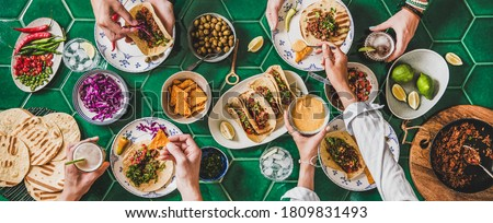 Friends home taco party. Flat-lay of Mexican traditional dishes Tacos with beef meat, corn tortillas , tomato salsa and peoples hands with food over green background, top view. Mexican cuisine