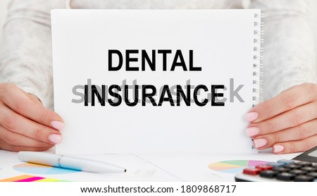 The girl holds a card with the inscription DENTAL INSURANCE.