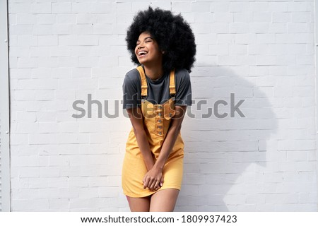 Happy stylish African American young woman wears yellow trendy sundress with Afro hair laughing looking away standing against white brick wall outdoor background. Smiling black hipster woman portrait Royalty-Free Stock Photo #1809937423