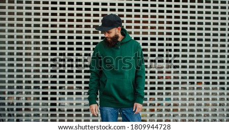 City portrait of handsome hipster guy with beard wearing green (watercolor) blank hoodie or sweatshirt with space for your logo or design. Mock up for print