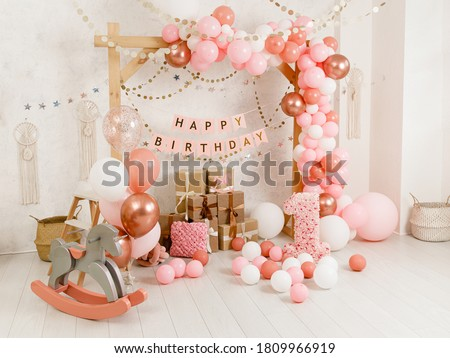 Birthday decorations - gifts, toys, balloons, garland and figure for little baby party on a white wall background.