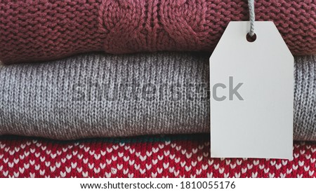 Knitted sweaters with empty card for price or text. Autumn, winter sale season. Close up, copy space, layout for design