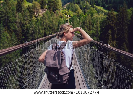 Side view of anonymous female backpacker in sporty outfit standing on sidewalk on bridge near green trees while exploring views #1810072774