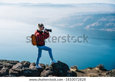 Side view of travelling woman in sunglasses and jeans standing on stone cliff near mountain lake while taking picture of landscape