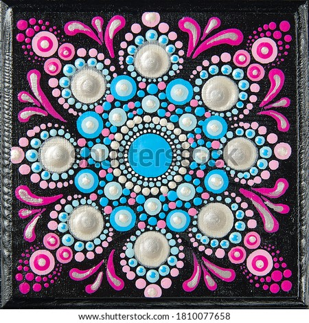 Mandala dot art painting on wood tiles. Beautiful mandala hand painted by colorful dots on black wood. National patterns with acrylic paints, handwork, dot painting. Abstract dotted background. #1810077658