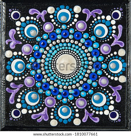 Mandala dot art painting on wood tiles. Beautiful mandala hand painted by colorful dots on black wood. National patterns with acrylic paints, handwork, dot painting. Abstract dotted background. #1810077661