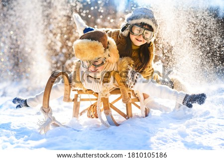 Two smiling children ride lying on a wooden retro sled on a sunny winter day. Active winter outdoors games. Happy Christmas vacation concept. Royalty-Free Stock Photo #1810105186