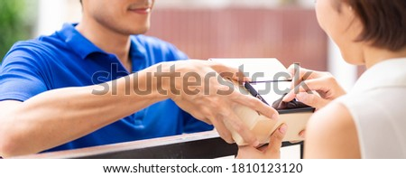 Panoramic Asian woman sign electronic signature to portable mobile device after receive packge from male delivery man in blue shirt. Package shopping delivery and digital sign concept.