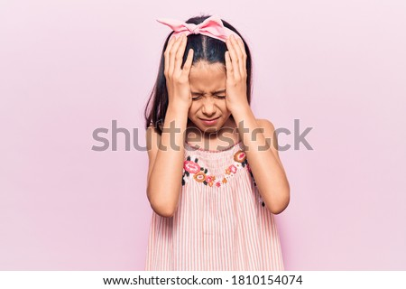 Beautiful child girl wearing casual clothes suffering from headache desperate and stressed because pain and migraine. hands on head.