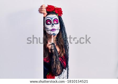 Young woman wearing day of the dead custome holding blank empty banner thinking concentrated about doubt with finger on chin and looking up wondering