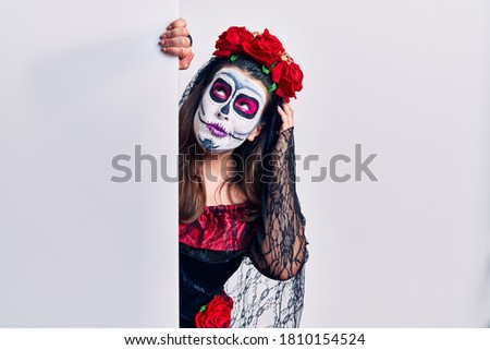 Young woman wearing day of the dead custome holding blank empty banner confuse and wondering about question. uncertain with doubt, thinking with hand on head. pensive concept.