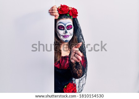 Young woman wearing day of the dead custome holding blank empty banner smiling friendly offering handshake as greeting and welcoming. successful business.