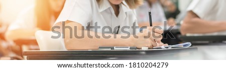 Exam at school with student's taking educational admission test in class, thinking hard, writing answer in university classroom, education and world literacy day concept Royalty-Free Stock Photo #1810204279