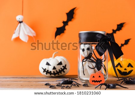 Funny Halloween day decoration party, Baby white ghost crafts scary face in jar glass and cute pumpkin ghost on wood table, studio shot isolated on orange background have spider and bats #1810231060