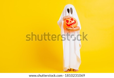 Funny Halloween Kid Concept, little cute child with white dressed costume halloween ghost scary he holding orange pumpkin ghost on hand, studio shot yellow on white background #1810231069
