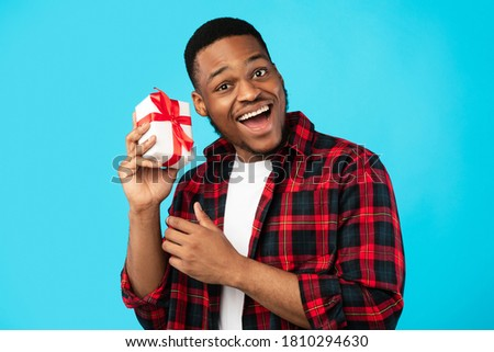 Excited Black Man Shaking Wrapped Gift Box Receiving Presents On His Birthday Standing Over Blue Background. Studio Shot Royalty-Free Stock Photo #1810294630