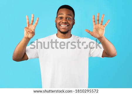 Black Man Showing Number Eight Counting On Fingers Standing Over Blue Background. Studio Shot #1810295572