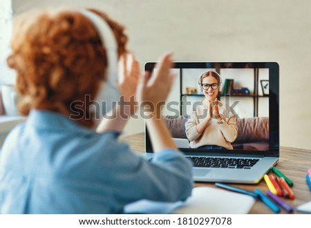 Anonymous  ginger boy in headphones sitting at table and listening to friendly teacher smiles and clap your hands during online lesson at home