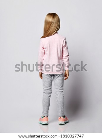 Cute smiling blonde kid girl in stylish smoked heart-shaped sunglasses and wool thermal underwear turtleneck shirt sweater and pants stands back to us over gray background. Back view