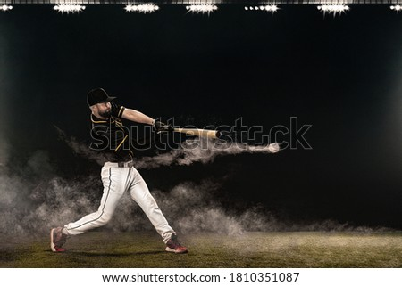 Baseball player with bat taking a swing on grand arena. Ballplayer on dark background in action. Royalty-Free Stock Photo #1810351087