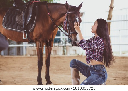 A beautiful Asian Thai woman with long hair and a Tartan shirt and jeans, she is kneeling and stroking the head of a horse lovingly and caring inside a stable in a ranch.