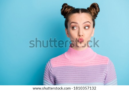Closeup photo of attractive teen lady two funny buns good mood charming cute nice youngster look side empty space sending air kisses wear casual warm sweater isolated blue color background Royalty-Free Stock Photo #1810357132
