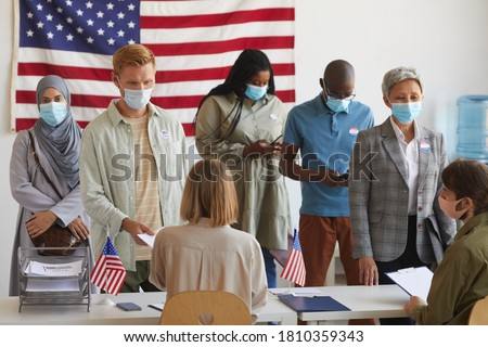 Multi-ethnic group of people standing in row and wearing masks at polling station on election day #1810359343