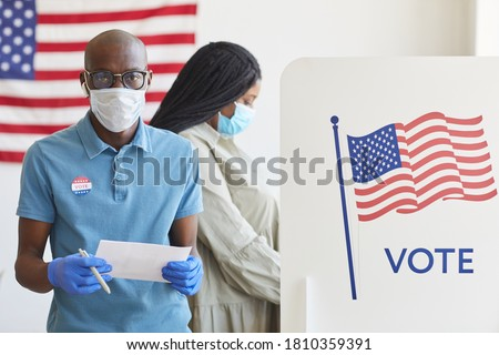 Waist up portrait of African-American man standing by voting booth decorated with USA flag and looking at camera on post-pandemic election day, copy space #1810359391