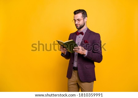 Portrait of his he nice attractive focused intellectual guy reading book academic learning free time knowledge library isolated over bright vivid shine vibrant yellow color background Royalty-Free Stock Photo #1810359991