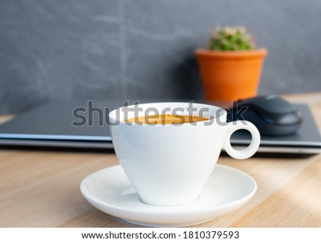 close up a cup of mornign coffee with laptop and mouse on grey background. Office lifestyle monday morning  modern women lifestyels