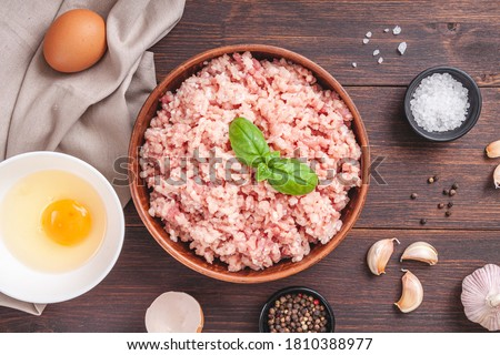 Raw minced meat in bowl on wooden table and ingredients. Ground meat with ingredients for cooking on dark background with copy space. Top view or flat lay Royalty-Free Stock Photo #1810388977