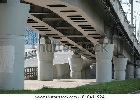 Bottom view of the concrete piers of the transport viaduct. Massive columns support the road bridge. Sunny day. High quality photo #1810411924