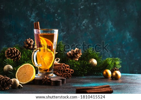 Christmas or New Year hot winter drink, spicy grog cocktail, punch or mulled wine with tea, lemon, rum, cinnamon, anise. Rustic style, festive table setting, copy space Royalty-Free Stock Photo #1810415524