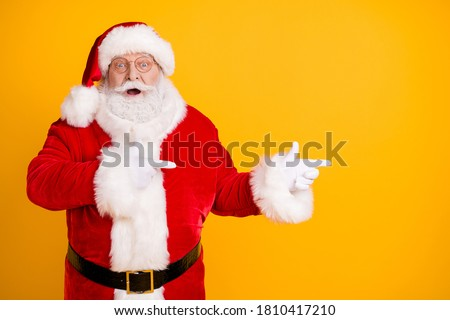 Photo astonished beard santa claus impressed x-mas  christmas adverts discount point finger copyspace wear cap headwear stylish trendy costume isolated bright shine color background