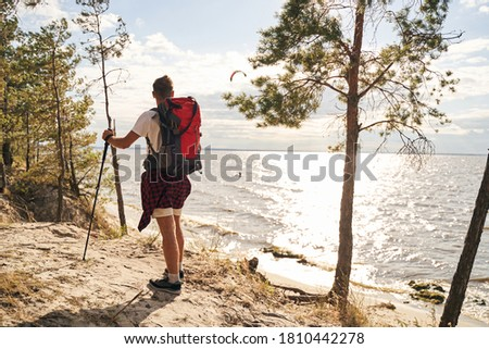 Sporty man is carrying backpack while hiking with trecking sticks in forest near sea shore #1810442278