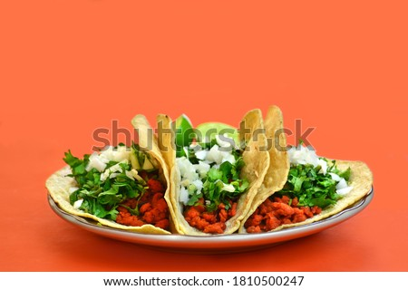 Frontal view of three delicious tacos with vegan meat and coriander, in orange background.
