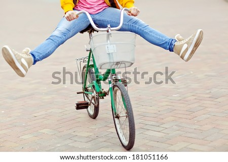 Woman riding bicycle with her legs in the air #181051166
