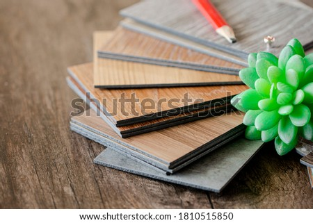 Luxury vinyl flooring tile collection : sample stack of vinyl sheet catalog on wooden table space for customer selection Royalty-Free Stock Photo #1810515850