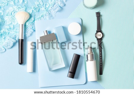 Women's cosmetics and accessories on a blue striped background: perfume, cream, lipstick, makeup brush. Fashion and Beauty Concept. #1810554670