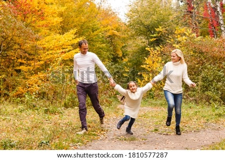 Picture of lovely family in autumn park, young parents with nice adorable daughter playing outdoors, have fun on backyard in fall, happy family enjoy autumnal nature