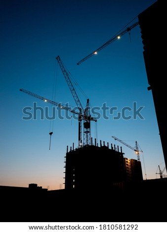 Construction crane at evening time on the blue sky with no clouds. Residential buildings construction at evening time minimalistic photo #1810581292