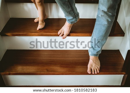 a little girl walking down the stairs hand in hand with her fath Royalty-Free Stock Photo #1810582183