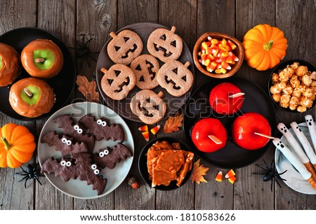 Rustic Halloween treat table scene over a dark wood background. Top view. Variety of candied apples, cookies, candy and sweets. #1810583626