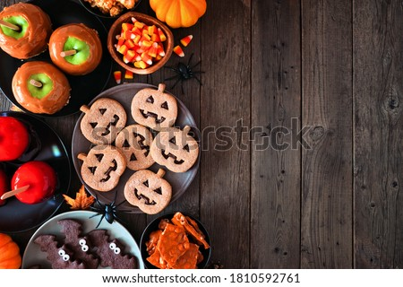 Rustic Halloween treat side border over a dark wood background with copy space. Top view. Variety of candied apples, cookies, candy and sweets. #1810592761